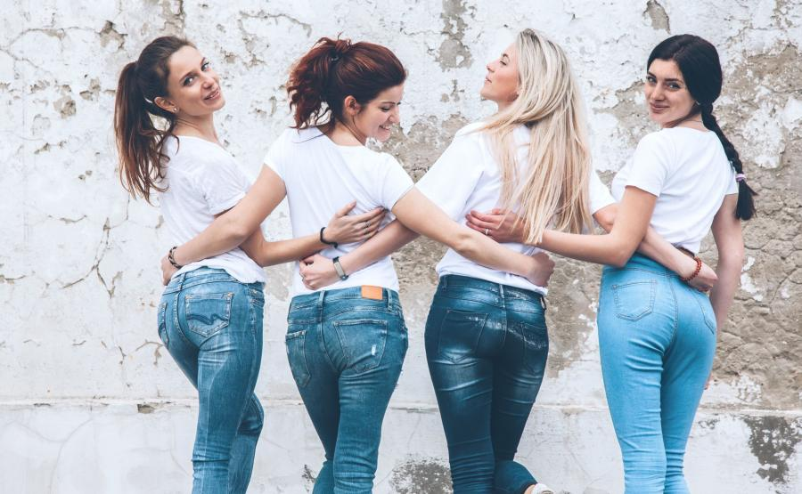 Kobiety w dżinsach odwrócone tyłem, plecami