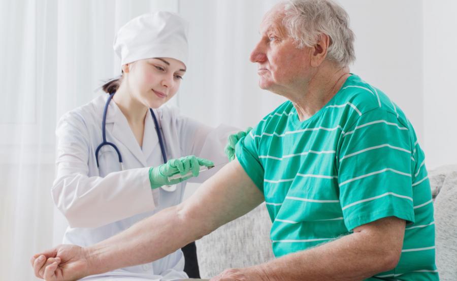 Szczepienie. Pielęgniarka szczepi starszego mężczyznę