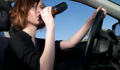 Kobieta pije alkohol za kierownicą