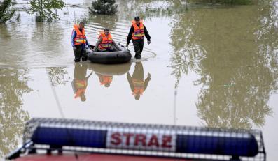 Strażacy transportują pontonem jedną z mieszkanek Buszkowic