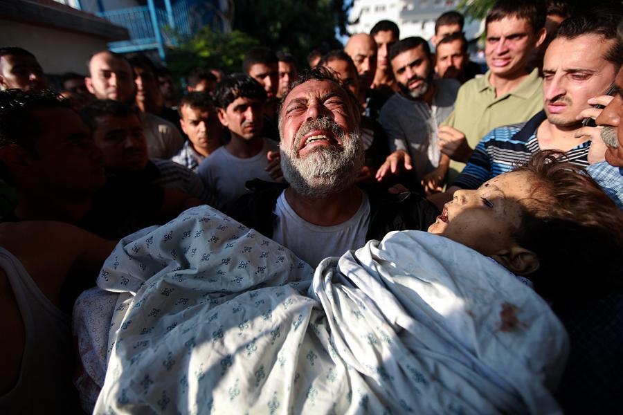 Akram Miqdad, ojciec sześcioletniego Bara-a, który zginął w ostrzale szpitala Szifa w Gazie, niesie ciało syna