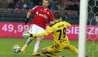 Piłkarz Wisły Kraków Paweł Brożek (L) w ataku na bramkę Sergiusza Prusaka (P) z Górnika Łęczna podczas meczu polskiej Ekstraklasy
