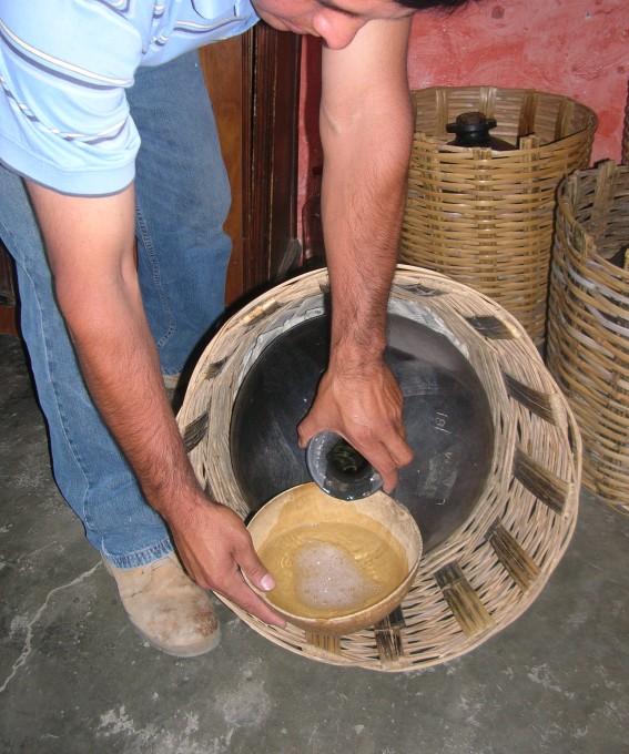 Mężczyzna nalewa meskal. Meksyk