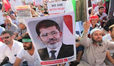 Tłum z plakatami z wizerunkiem Mohammeda Mursiego