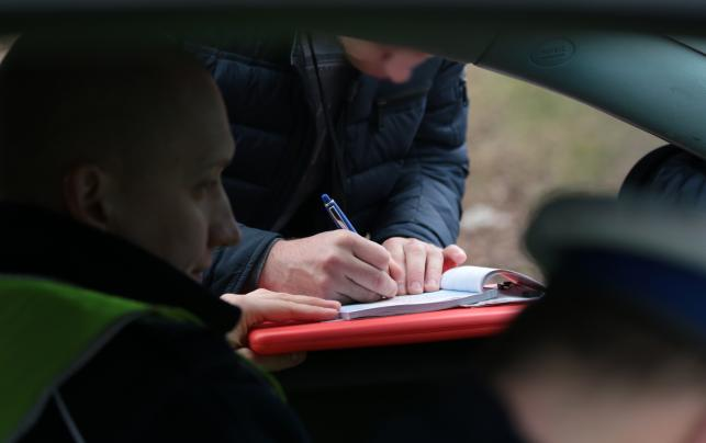 Kierowca podpisuje mandat