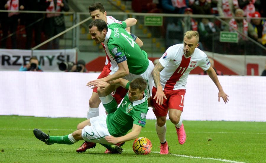 Gracze reprezentacji Polski Kamil Grosicki (P) i Robert Lewandowski (L - tył) oraz Seamus Coleman (dół) i John O'Shea (C) z Irlandii w meczu grupy D eliminacji piłkarskich mistrzostw Europy 2016