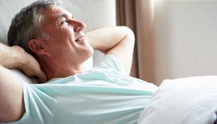 Uśmiechnięty mężczyzna leży w łóżku