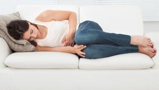 Kobieta leży z bólem brzucha