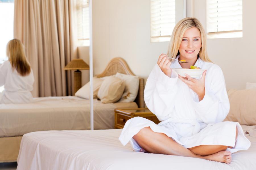 Kobieta je sałatkę owocową w łóżku