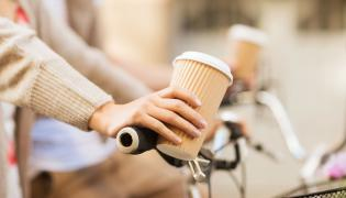 Kobieta na rowerze trzyma kubek z kawą