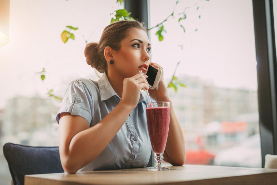 Kobieta pije kolorowe smoothie